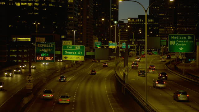 high angle medium zoom out traffic on highway in seattle at dusk - コロンビアセンター点の映像素材/bロール