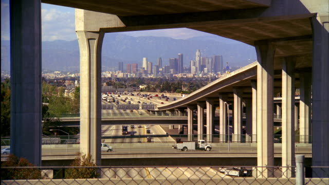 vídeos de stock, filmes e b-roll de ws, ha, traffic on highway, skyline of downtown los angeles in background, sunset, california, usa - fan palm tree
