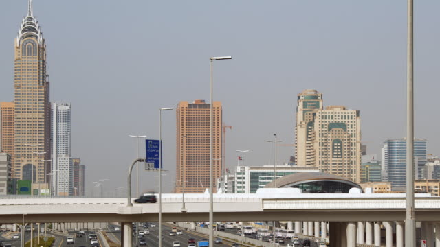 vídeos de stock, filmes e b-roll de t/l traffic on highway with city skyline in the background / dubai, united arab emirates - formato letterbox
