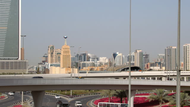 stockvideo's en b-roll-footage met t/l traffic on highway with city skyline in the background / dubai, united arab emirates - breedbeeldformaat