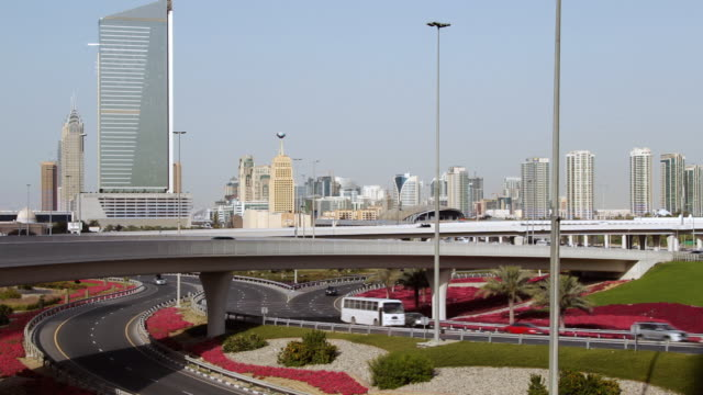 vídeos de stock, filmes e b-roll de ha traffic on highway with city skyline in the background / dubai, united emirates - formato letterbox