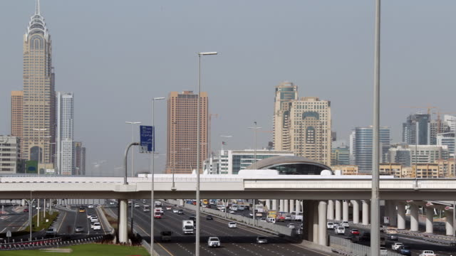 ha traffic on highway with city skyline in the background / dubai, united emirates - breitwandformat stock-videos und b-roll-filmmaterial