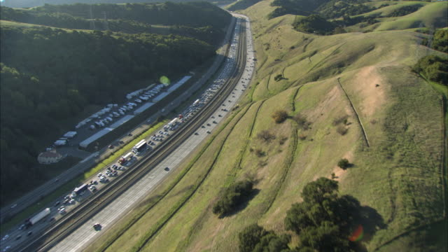 aerial traffic on highways crossing green hills / san francisco, california, usa - nordkalifornien stock-videos und b-roll-filmmaterial