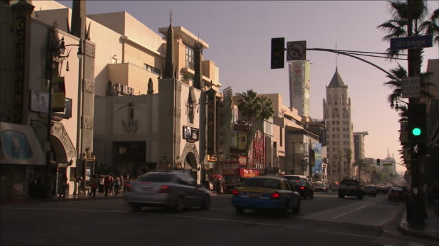 traffic on hollywood boulevard passes grauman's chinese theatre. - mann theaters stock videos & royalty-free footage
