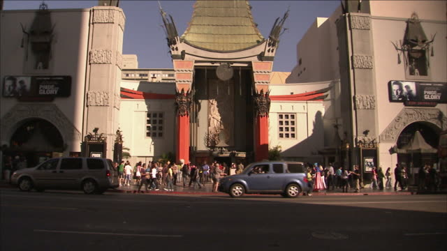 traffic on hollywood boulevard passes tourists in front of grauman's chinese theatre. - tlc chinese theater bildbanksvideor och videomaterial från bakom kulisserna