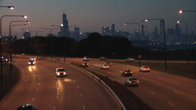ws ha traffic on lake shore drive at dusk, city skyline in background / chicago, illinois, usa - traffic点の映像素材/bロール