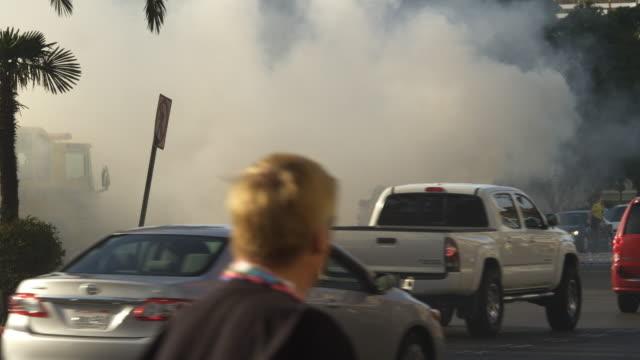 traffic on las vegas boulevard passing a firefighter hosing down a burning car - artbeats bildbanksvideor och videomaterial från bakom kulisserna