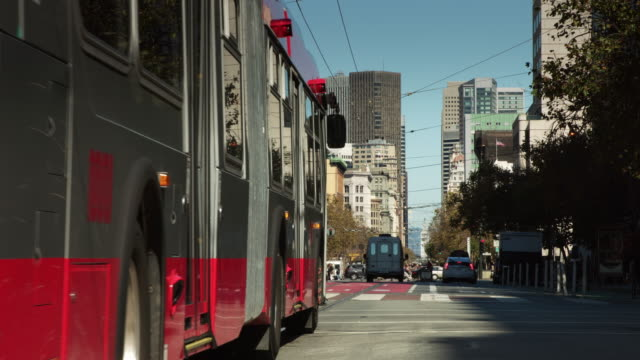 traffic on market street, san francisco with passing trolley bus - trolley bus stock videos & royalty-free footage