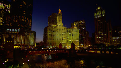 wide shot traffic on michigan avenue bridge and chicago river in front of wrigley-building, trump tower, and tribune tower at night - torre del tribune video stock e b–roll