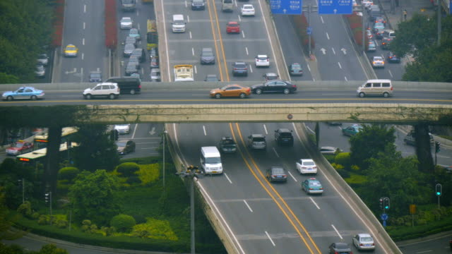 traffic on multi level city highway intersection in guangzhou. narrow shot from above - spoonfilm stock-videos und b-roll-filmmaterial