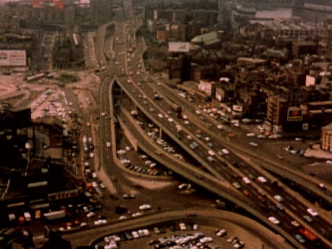 1960 HA traffic on multi-lane highway and overpasses running through city / USA