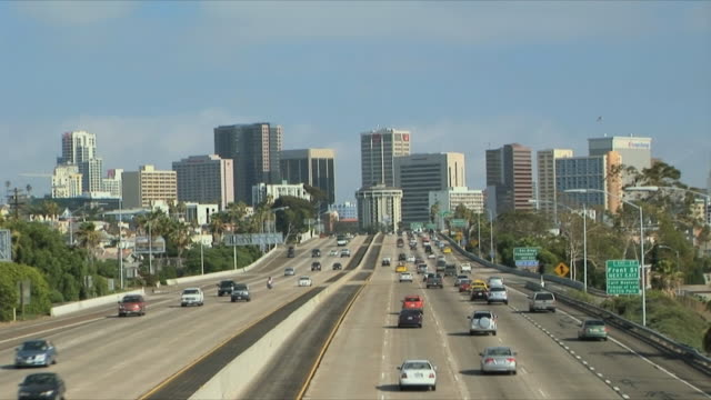 WS Traffic on multiple lane freeway towards city downtown, commercial plane descending over highway, San Diego, California, USA