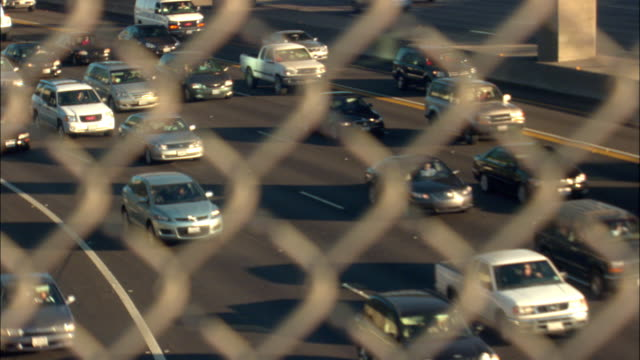 ms ha selective focus, traffic on multiple lane highway through chain link fence, los angeles, california, usa - wire mesh fence stock videos & royalty-free footage