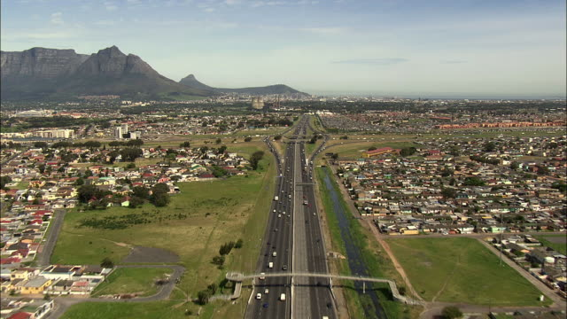 T/L AERIAL Traffic on N7 road with Table Mountain and downtown skyscrapers, Cape Town, Western Cape, South Africa