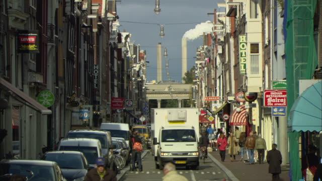 WS Traffic on narrow street, smokestacks emitting white smoke in background / Amsterdam, Holland