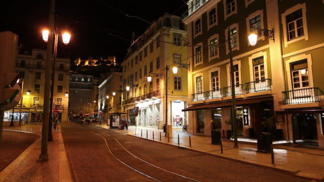 ws traffic on old town street at night / lisbon, portugal - campo totale video stock e b–roll