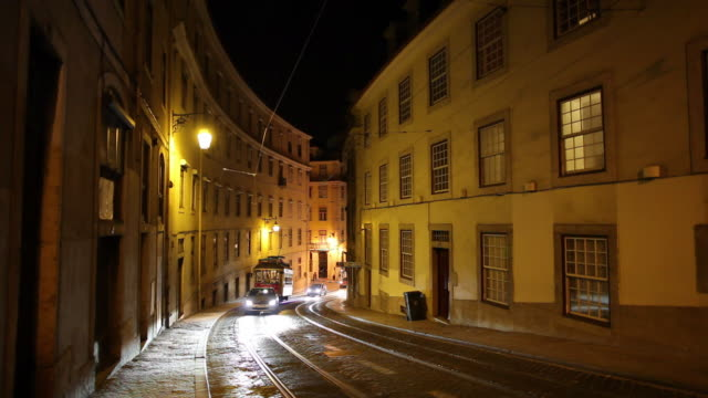 ws traffic on old town street at night / lisbon, portugal - narrow stock videos and b-roll footage