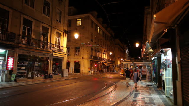 WS Traffic on old town street at night / Lisbon, Portugal