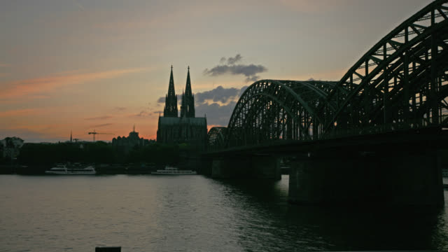 TIME LAPSE WIDE SHOT traffic on Rhine River and Hohenzollern Bridge with Cologne Cathedral in background at sunset, Cologne, Germany