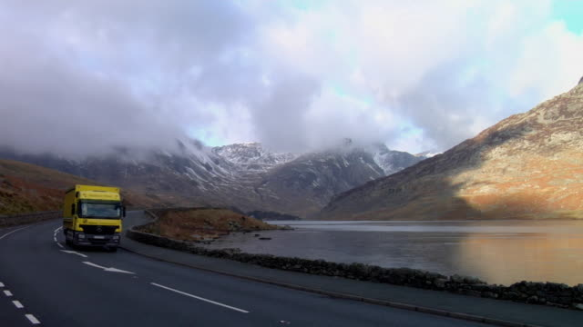 ws traffic on road beside lake, snowcapped mountains in background / capel curig, snowdonia, uk - loopable elements stock videos & royalty-free footage