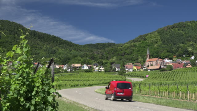 vidéos et rushes de traffic on road through vineyard - village