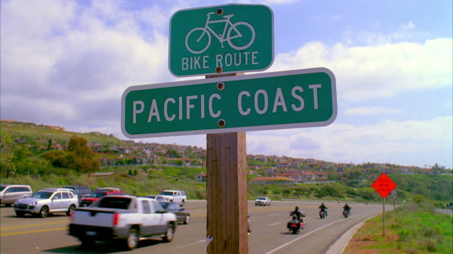 ws traffic on road with bike route sign on foreground / monarch bay, california, usa - laguna beach california video stock e b–roll