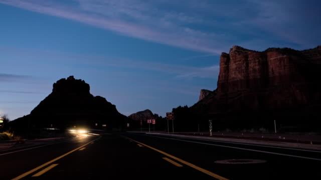 T/L WS Traffic on rural highway between red rocks at night, Sedona, Arizona, USA