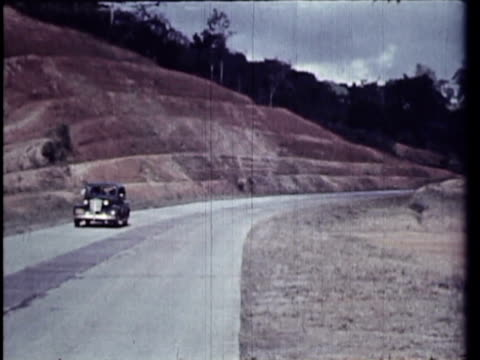 1958 MS WS MONTAGE Traffic on rural highway, people walking on street by shops / Calobre, Panama / AUDIO