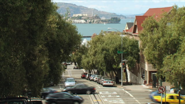vidéos et rushes de ws tu traffic on san francisco street, alcatraz island in background / california, usa - baie de san francisco