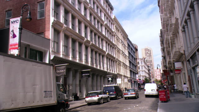 LA Traffic on SoHo street passing buildings with cast-iron architecture / New York City, New York, United States