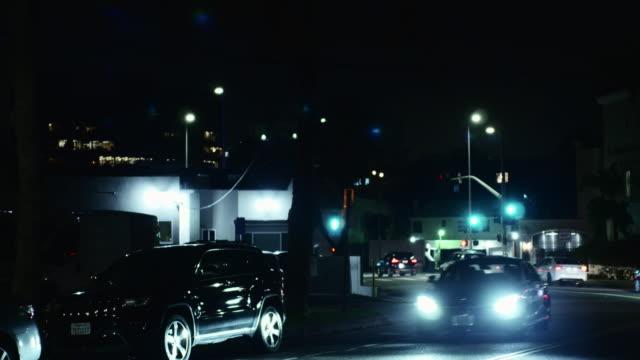 traffic on street at night mid-wilshire - neighborhood street sign stock videos and b-roll footage