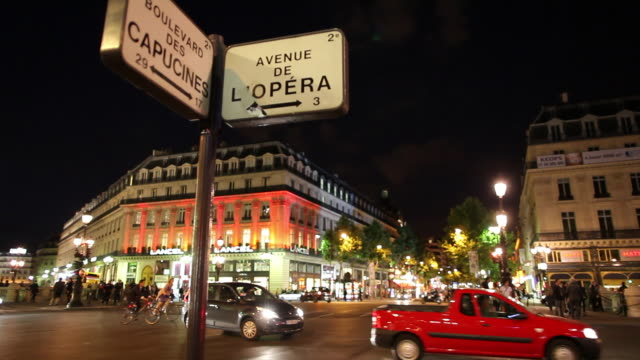 ws traffic on street at night, street name signs in foreground / paris, france - street name sign stock-videos und b-roll-filmmaterial