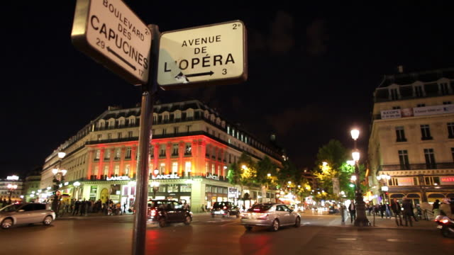 ws traffic on street at night, street name signs in foreground / paris, france - straßenschild stock-videos und b-roll-filmmaterial