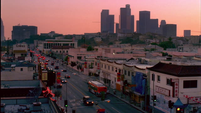 WS, HA, Traffic on street in Chinatown at early evening, downtown skyline in background, Los Angeles, California, USA
