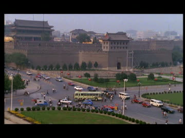 stockvideo's en b-roll-footage met ha, traffic on street intersection at ancient city gate and wall, xian, shaanxi province, china - 1999