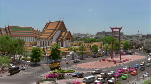 MS, HA, Traffic on street, temple in background, Bangkok, Thailand