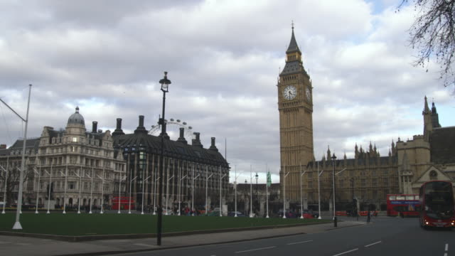 ws pan traffic on street with big ben and parliament in background, london, united kingdom - ビッグベン点の映像素材/bロール