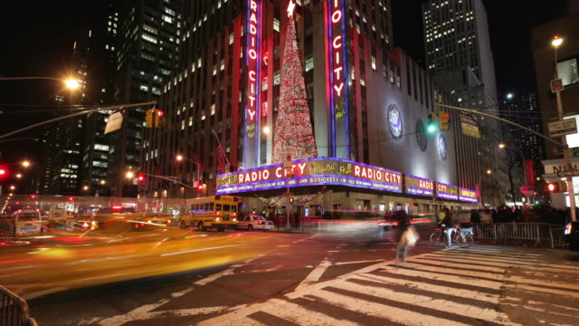 ws tu t/l traffic on street with radio city music hall and christmas tree twinkling next to neon signs / new york city, new york, usa - radio city music hall stock videos & royalty-free footage