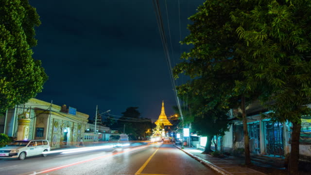 traffic on street with shwedagon pagoda as background at night, time lapse video - shrine stock videos & royalty-free footage