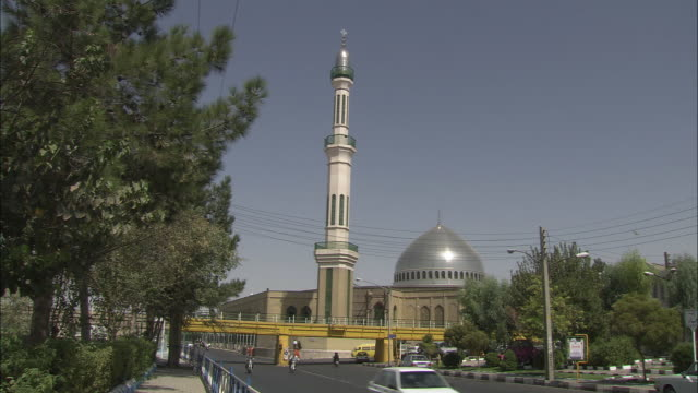 WS Traffic on street with silver domed mosque in background / Qom, Iran