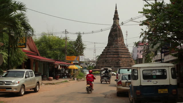 ws traffic on street with stupa in background / vientiane, laos - stupa stock videos & royalty-free footage