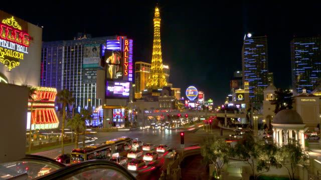 time lapse wide shot traffic on strip past ballys and paris las vegas at night - paris las vegas stock videos & royalty-free footage