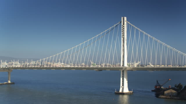 traffic on the bay bridge with port of oakland beyond - oakland california stock videos & royalty-free footage