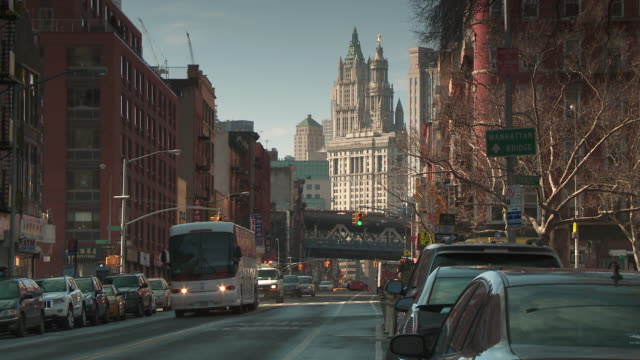 traffic on the east side of manhattan by madison street & rutgers street in new york city.  the woolworth building is behind and the manhattan bridge is in the middle of the frame. - manhattan new york city stock videos & royalty-free footage