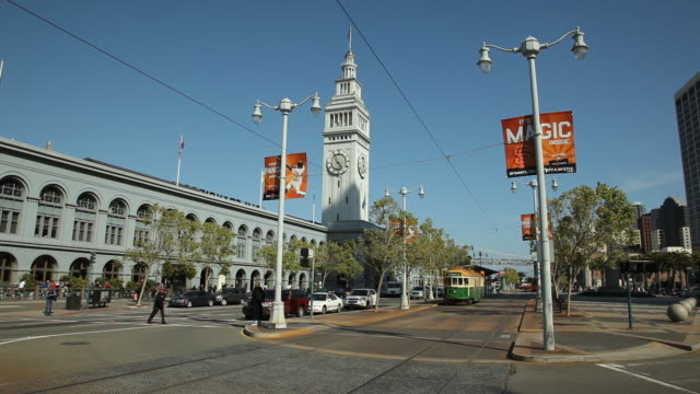 ws pan traffic on the embarcadero with ferry building in background / san francisco, california, usa - フェリーターミナル点の映像素材/bロール