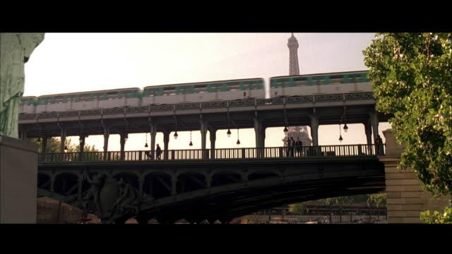 stockvideo's en b-roll-footage met pan traffic on the pont de bir-hakeim bridge with eiffel tower beyond / paris, france - breedbeeldformaat