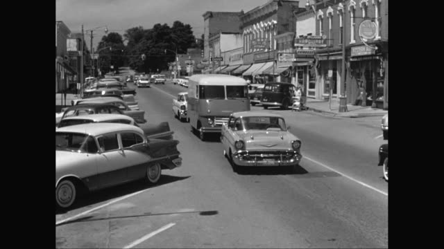 ws pan traffic on the street in small town business district / united states - american culture stock videos and b-roll footage