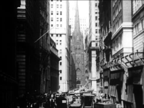 vídeos de stock, filmes e b-roll de traffic on wall street with trinity church in background / nyc / newsreel - 1920 1929