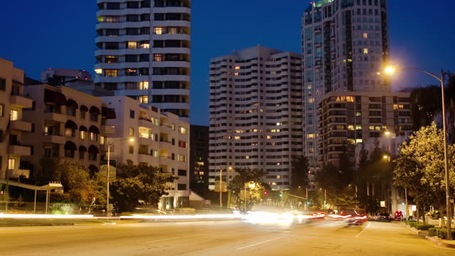 vídeos de stock e filmes b-roll de t/l ws traffic on wilshire boulevard with condominium and coop buildings at night, los angeles, california, usa - bulevar