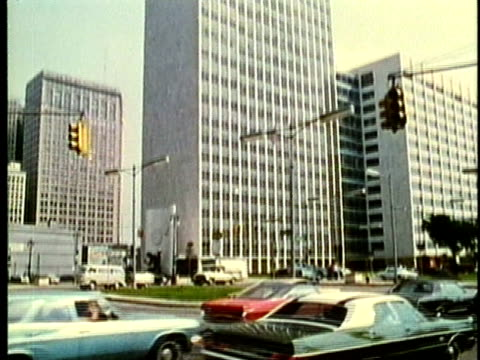 vidéos et rushes de montage, traffic on woodward avenue with skyscrapers and spirit of detroit monument in background, 1960's, detroit, michigan, usa - 1960 1969